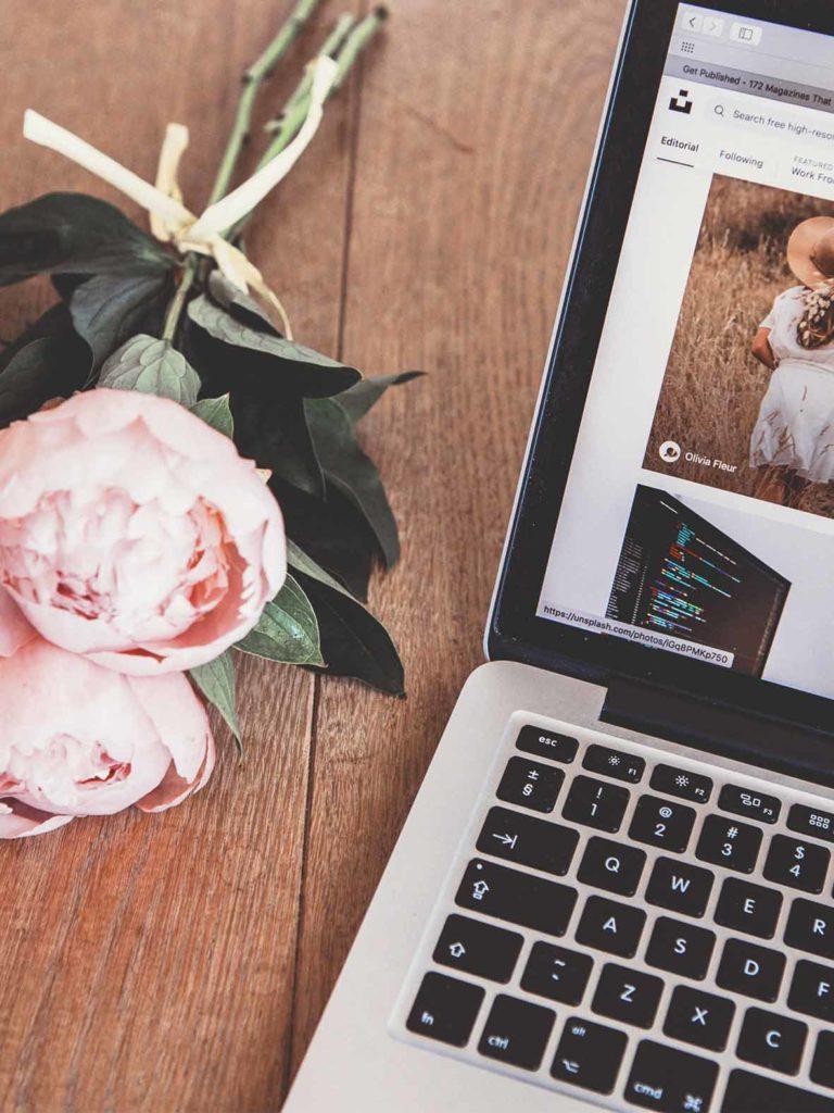 laptop su tavolo di legno con mazzo di fiori rosa