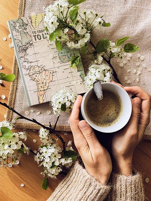 Tazza di caffe con mani e fiori Emanuela Bloomie Asti