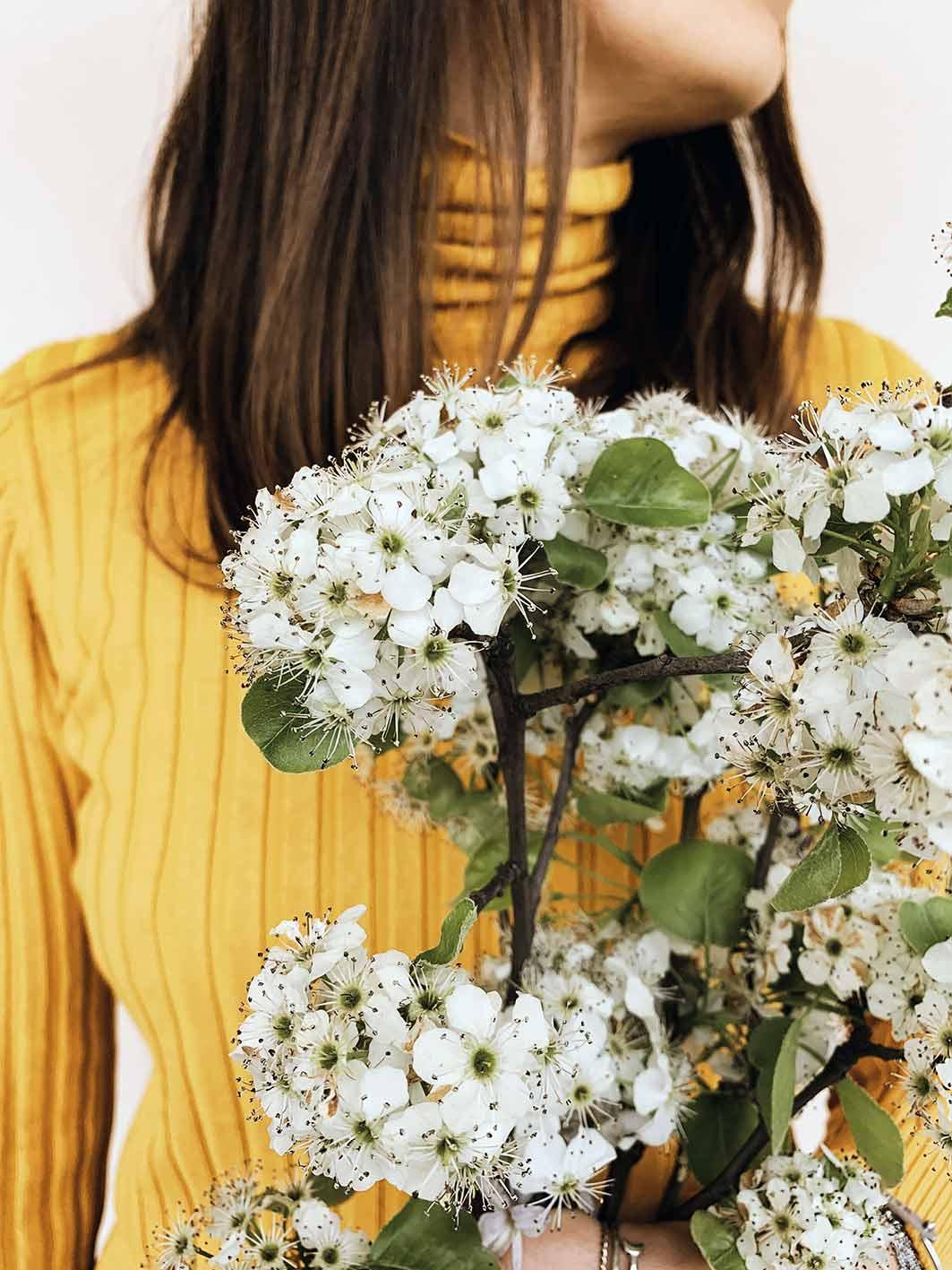 Emanuela Bloomie ragazza con mazzo di fiori bianchi e maglia gialla